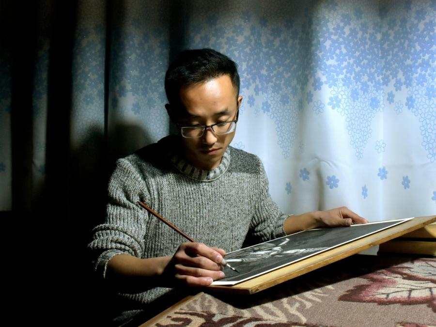 Liu Kai works on a pen-and-ink painting in 2017. (Photo provided to chinadaily.com.cn)