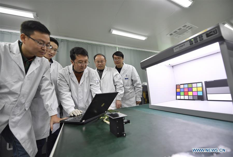 Staff members of Institute of Optics and Electronics of the Chinese Academy of Sciences examine the topographical camera installed on the lander of the Chang\'e-4 probe in Chengdu, southwest China\'s Sichuan Province, Jan. 17, 2019. The topographical camera installed on the lander of the Chang\'e-4 probe is responsible for both taking colorful high-resolution images on the lunar surface and monitoring the lunar rover Yutu-2. China\'s Chang\'e-4 lunar probe, comprising a lander and a rover, landed on the far side of the moon on Jan. 3, 2019. (Xinhua/Liu Kun)