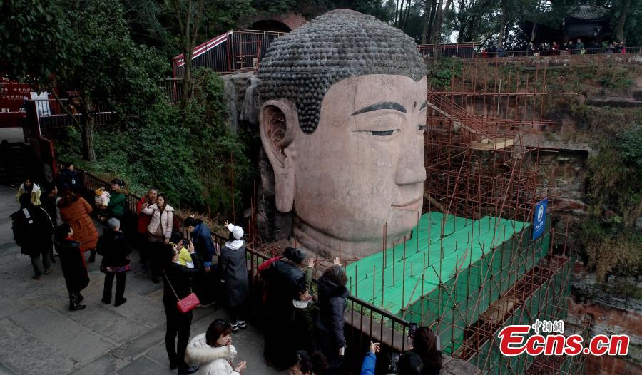 Photo taken on Jan. 17, 2019 shows the Leshan Giant Buddha statue undergoing restoration work in Leshan City, Southwest China\'s Sichuan Province. The 71-meter-tall statue, carved in the 8th century on a hillside overlooking the confluence of three rivers, is the largest Buddhist sculpture in the world. (Photo: China News Service/Liu Zhongjun)