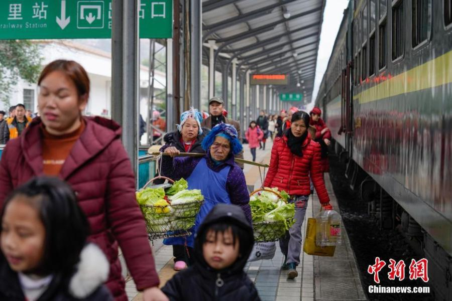 Passengers carrying agricultural products alight a train at Kaili Railway Station in Guizhou Province, Jan. 17, 2019. The railway line linking Guiyang City and Yuping County in Tongren County has been running for 44 years - opening in 1975 - connecting the villages of the many ethnic groups residing deep in the mountains with the outside world. The 342-km journey takes about seven hours - incredibly slow when compared with the speeds of China\'s increasingly ubiquitous bullet trains. (Photo: China News Service/He Junyi)