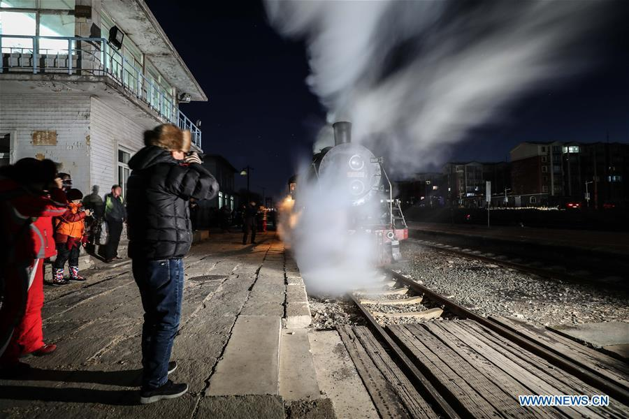 Visitors take pictures of a steam locomotive leaving Diaobingshan Station, northeast China\'s Liaoning Province on Jan. 17, 2019. A 5-day steam locomotive tourism event kicked off in Diaobingshan on Thursday. Tourists can visit the steam locomotive museum, take pictures of steam locomotives and watch exhibitions during the event. (Xinhua/Pan Yulong)