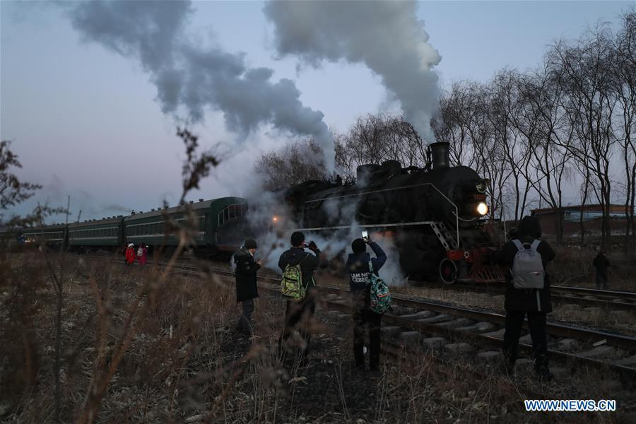 Visitors take pictures of a steam locomotive heading to the steam locomotive museum of Tiefa Energy Co., Ltd from Diaobingshan Station, northeast China\'s Liaoning Province on Jan. 17, 2019. A 5-day steam locomotive tourism event kicked off in Diaobingshan on Thursday. Tourists can visit the steam locomotive museum, take pictures of steam locomotives and watch exhibitions during the event. (Xinhua/Pan Yulong)