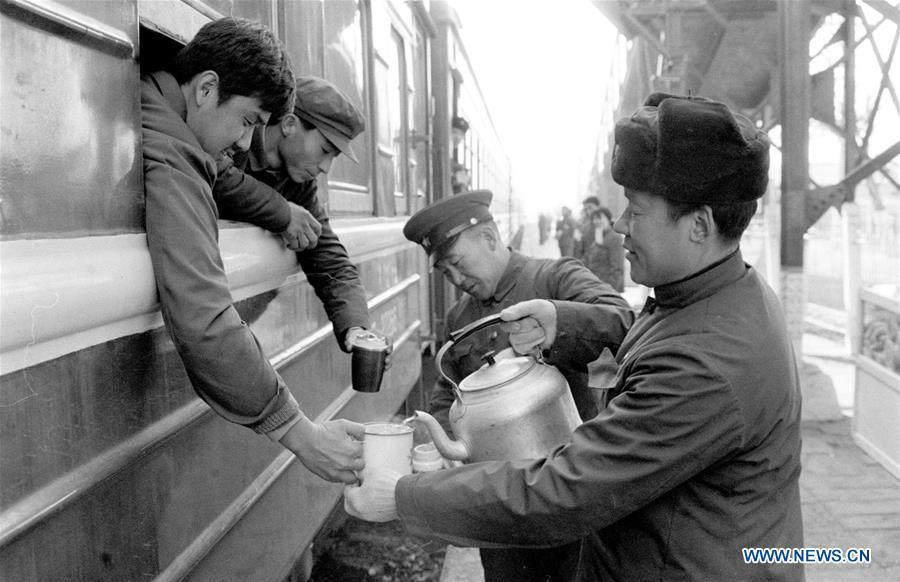 Staff members of the Shijiazhuang Railway Station pour hot water into passengers\' cups during the Spring Festival travel rush in Shijiazhuang, north China\'s Hebei Province, in the year of 1984. Returning to hometowns remains the most important part of the Chinese Spring Festival. Whether self-driving, or taking the trains or flights, homecomings and family gatherings are a priority for many Chinese. The annual travel rush around the festival, known as \