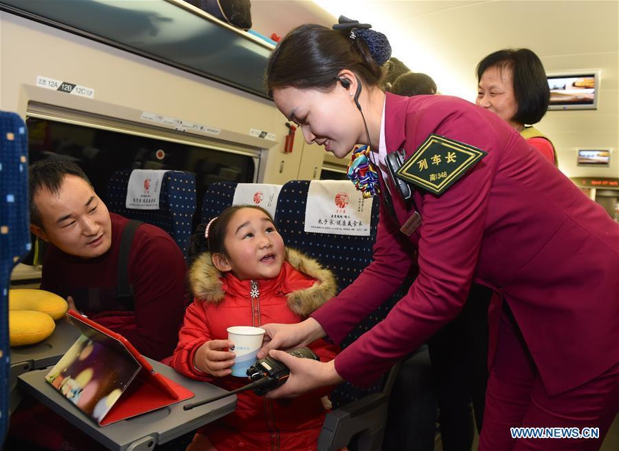 Train conductor Liao Hui (R) with Fuzhou sector of Nanchang\'s Railway Bureau brings hot water to passengers during the Spring Festival travel rush on Feb. 6, 2016. Returning to hometowns remains the most important part of the Chinese Spring Festival. Whether self-driving, or taking the trains or flights, homecomings and family gatherings are a priority for many Chinese. The annual travel rush around the festival, known as \