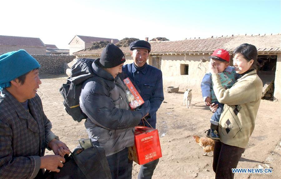 Migrant worker Chu Mingdong (2nd, L) is received by his family as he returns home for the Spring Festival family reunion in Mijiagou Village, Zhangbei County of north China\'s Hebei Province, Feb. 10, 2002. Returning to hometowns remains the most important part of the Chinese Spring Festival. Whether self-driving, or taking the trains or flights, homecomings and family gatherings are a priority for many Chinese. The annual travel rush around the festival, known as \