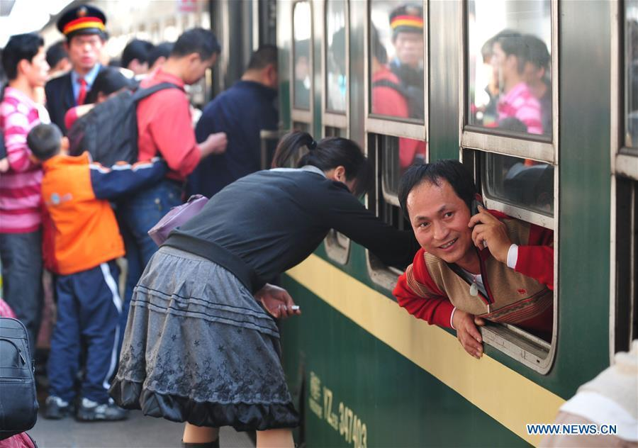A passenger calls home as soon as he gets on the train at Guangzhou Railway Station in Guangzhou, south China\'s Guangdong Province, Jan. 22, 2009. Returning to hometowns remains the most important part of the Chinese Spring Festival. Whether self-driving, or taking the trains or flights, homecomings and family gatherings are a priority for many Chinese. The annual travel rush around the festival, known as \
