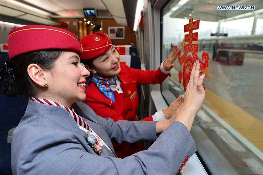 A foreign volunteer and the train staff member decorate the train cabin at Xi\'an North Railway Station in Xi\'an, capital of northwest China\'s Shaanxi Province, Jan. 20, 2019. Three foreign student volunteers from Xi\'an Jiaotong University came to Xi\'an North Railway Station on Sunday to familiarize themselves with the train staff members\' work. They would serve passengers during the Spring Festival travel rush. The Spring Festival, or the Year of the Pig in the Chinese lunar calendar, will begin on Feb. 5 this year. The 40-day 2019 Spring Festival travel rush started on Jan. 21, with 3 billion trips expected to be made. (Xinhua/Tang Zhenjiang)