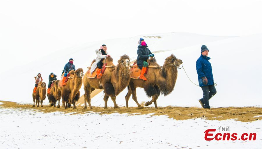 Tourists ride camels at the Crescent Spring and Singing-Sand Dunes scenic spot in Dunhuang City, Northwest China\'s Gansu Province, Jan. 19, 2019, after the area\'s first snow for the year. (Photo: China News Service/Wang Binyin)