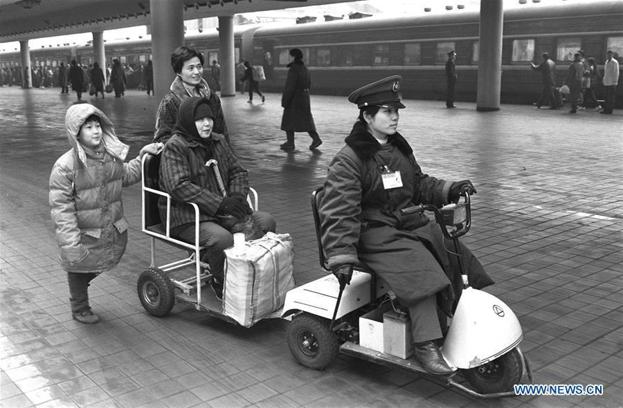 Staff member Xu Xin sends senior passenger Zhou Fengying to her train at the Beijing Railway Station in Beijing, capital of China, Jan. 30, 1994. Returning to hometowns remains the most important part of the Chinese Spring Festival. Whether self-driving, or taking the trains or flights, homecomings and family gatherings are a priority for many Chinese. The annual travel rush around the festival, known as \