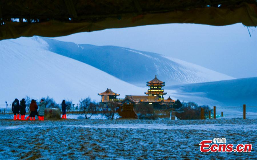The Crescent Spring and Singing-Sand Dunes scenic spot in Dunhuang City, Northwest China\'s Gansu Province, after its first snow of the year, Jan. 19, 2019. Riding a camel across the desert landscape has become a popular activity for tourists to the area. (Photo: China News Service/Wang Binyin)