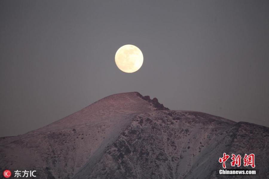 The first full moon of the new year is seen above the Tianshan Mountains in Xinjiang Uygur Autonomous Region, Jan. 20, 2019. (Photo/IC)