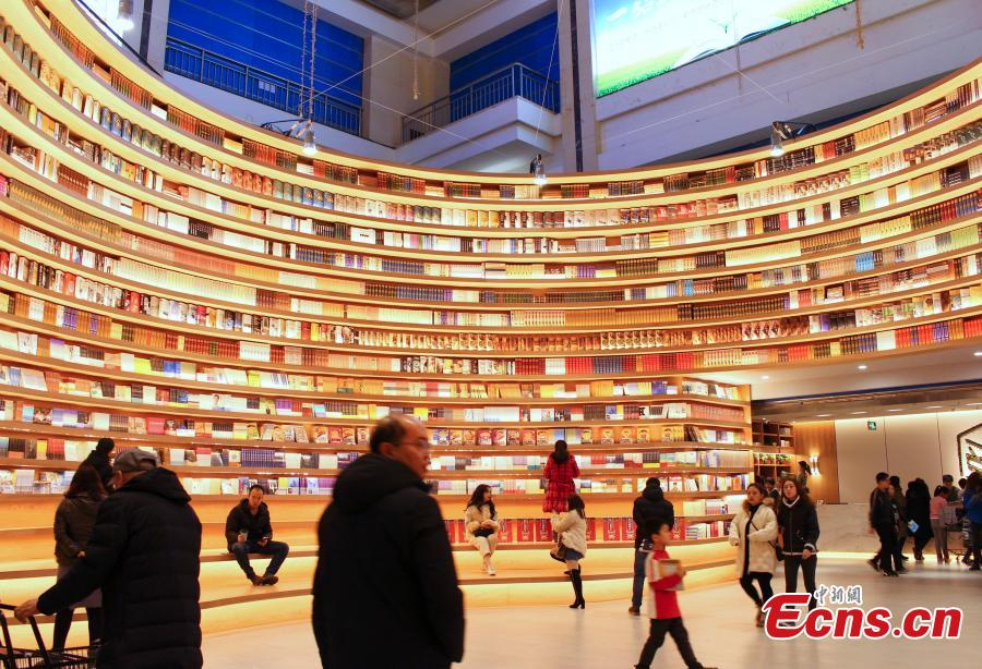 A circular wall stacked with books at a new bookstore in Hohhot, North China\'s Inner Mongolia Autonomous Region, Jan. 20, 2019. The innovative wraparound shelving units have attracted the interest of many visitors. (Photo: China News Service/Chen Feng)