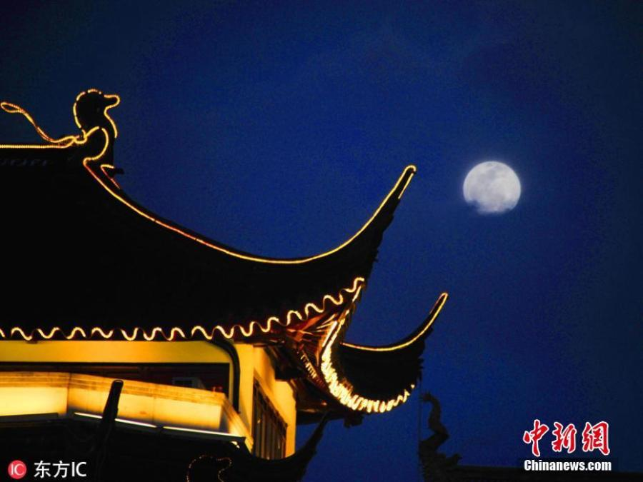 The first full moon of the new year appears beside a building in Yuyuan Garden, Shanghai, Jan. 20, 2019. (Photo/IC)