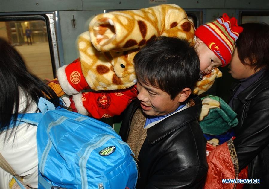 A passenger carrying his child on shoulder gets on a special train for migrant workers at the Beijing West Railway Station in Beijing, capital of China, Jan. 14, 2005. Returning to hometowns remains the most important part of the Chinese Spring Festival. Whether self-driving, or taking the trains or flights, homecomings and family gatherings are a priority for many Chinese. The annual travel rush around the festival, known as \