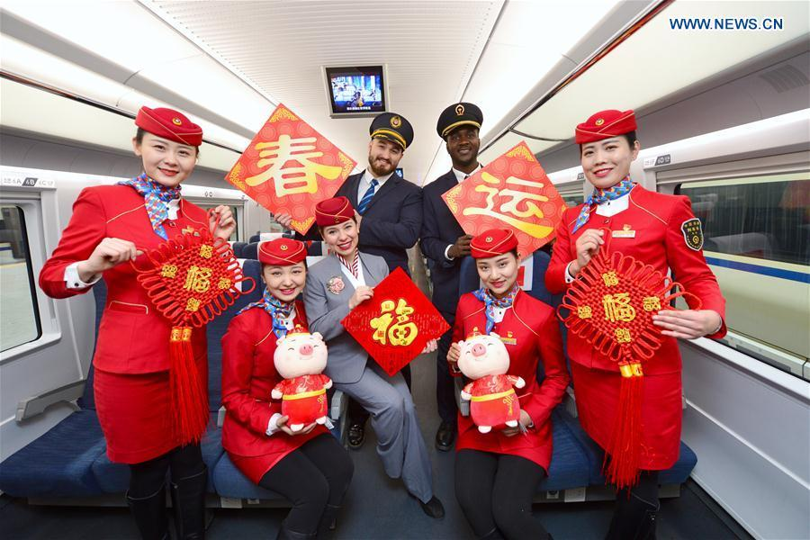 Train staff members pose for photos with foreign volunteers at Xi\'an North Railway Station in Xi\'an, capital of northwest China\'s Shaanxi Province, Jan. 20, 2019. Three foreign student volunteers from Xi\'an Jiaotong University came to Xi\'an North Railway Station on Sunday to familiarize themselves with the train staff members\' work. They would serve passengers during the Spring Festival travel rush. The Spring Festival, or the Year of the Pig in the Chinese lunar calendar, will begin on Feb. 5 this year. The 40-day 2019 Spring Festival travel rush started on Jan. 21, with 3 billion trips expected to be made. (Xinhua/Tang Zhenjiang)