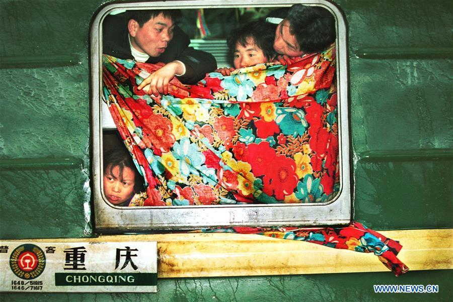 Passengers look outside through a windshielding bedsheet on a train at the Hankou Railway Station, central China\'s Hubei Province, Jan. 21, 2001. Returning to hometowns remains the most important part of the Chinese Spring Festival. Whether self-driving, or taking the trains or flights, homecomings and family gatherings are a priority for many Chinese. The annual travel rush around the festival, known as \
