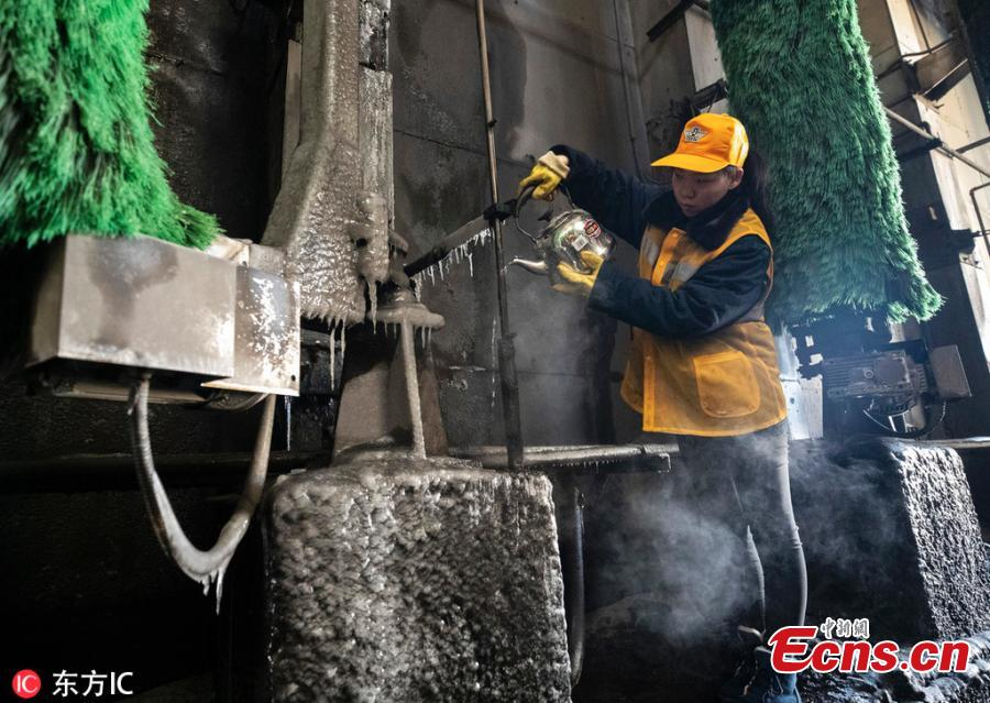 Female workers clean a train at a railway service station in Zhengzhou City, Central China\'s Henan Province. With an average age of 38 years, the workers in the cleaning unit are all female, with the exception of their male head. They are facing an increasing workload due to the Spring Festival travel rush, despite sub-zero temperatures. (Photo/IC)