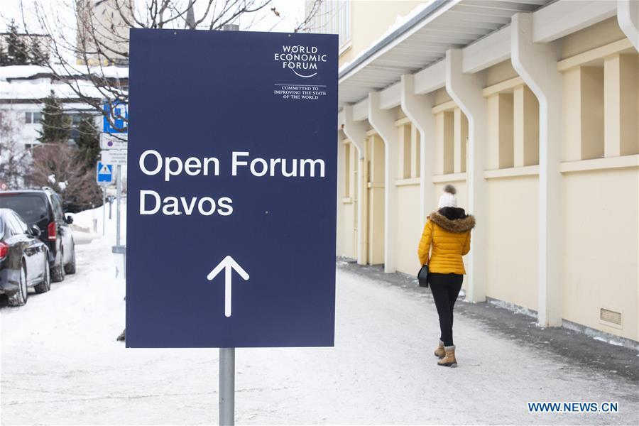 A woman passes by a sign of the World Economic Forum (WEF) in Davos, Switzerland, Jan. 21, 2019. The WEF Annual Meeting will kick off in Davos on Tuesday. (Xinhua/Xu Jinquan)