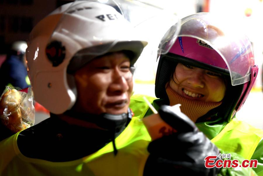 Liu Rongchun and his wife, migrant workers in Fujian Province, take a rest while riding a motorcycle back to their hometown of Shangrao in Jiangxi Province. (Photo: China News Service/Wang Dongming)