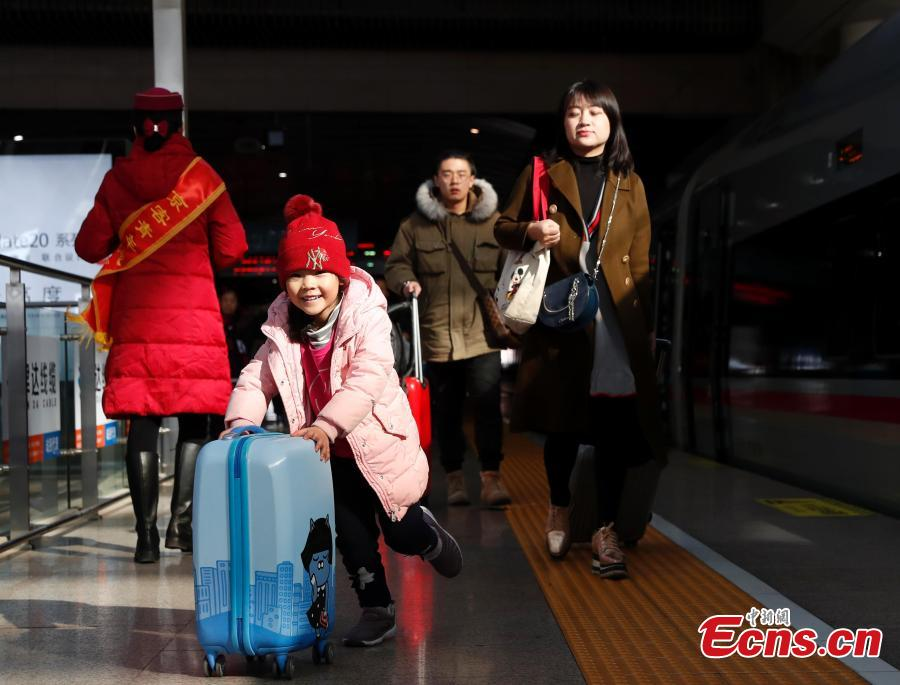 Passengers board a high-speed train at a railway station in Beijing, Jan. 21, 2019. (Photo: China News Service/Liu Guanguan)