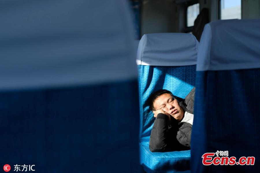 A passenger sleeps on a train traveling from Beijing to Zhuozhou in Hebei Province. (Photo/IC)