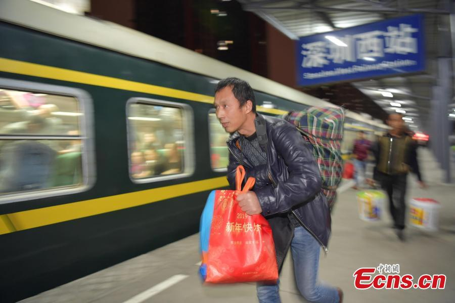 A passenger rushes to board a train at a railway station in Shenzhen City, Guangdong Province. (Photo: China News Service/Chen Wen)