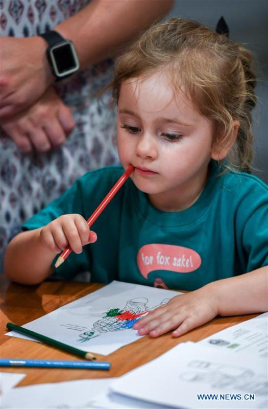 A girl contemplates while coloring a Chinese dragon in Te Papa, the national museum of New Zealand in Wellington, New Zealand, Jan. 23, 2019. A family event, with a theme on \