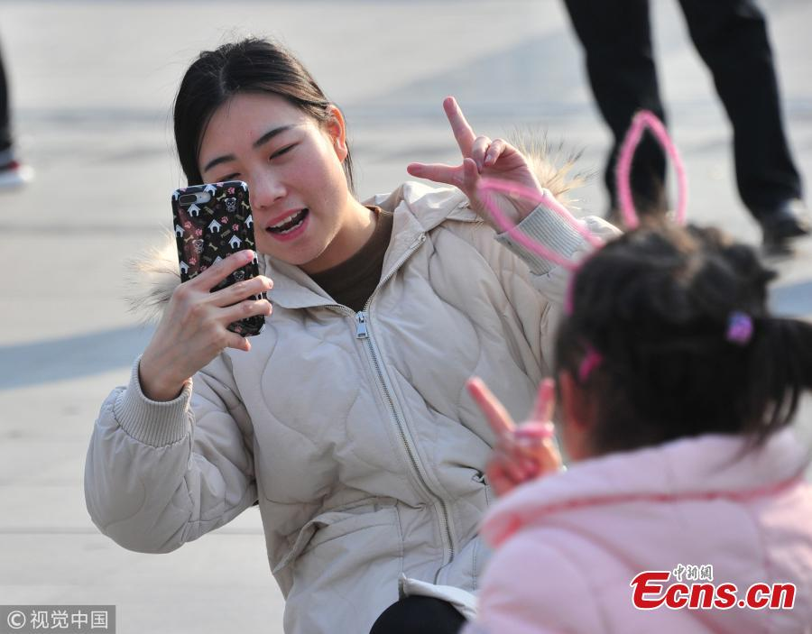 A mother takes a picture of her daughter at a railway station in Shanghai. (Photo/VCG)