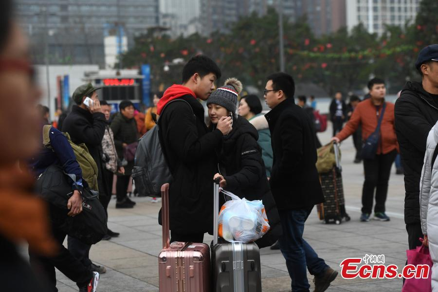 A student couple hugs each other at a railway station in Chongqing. (Photo: China News Service/Chen Chao)