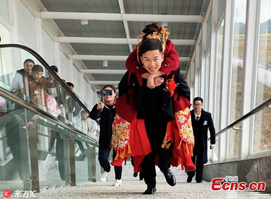 He Xueqiang carries his bride on his back to board a high-speed train at a railway station in Guangnan County, Yunnan Province. (Photo/IC)