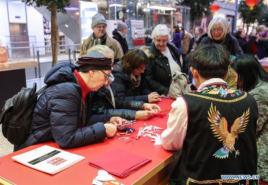 Visitors learn traditional Chinese paper cutting in a shopping mall at Potsdamer Platz in Berlin, capital of Germany, on Jan. 24, 2019. \