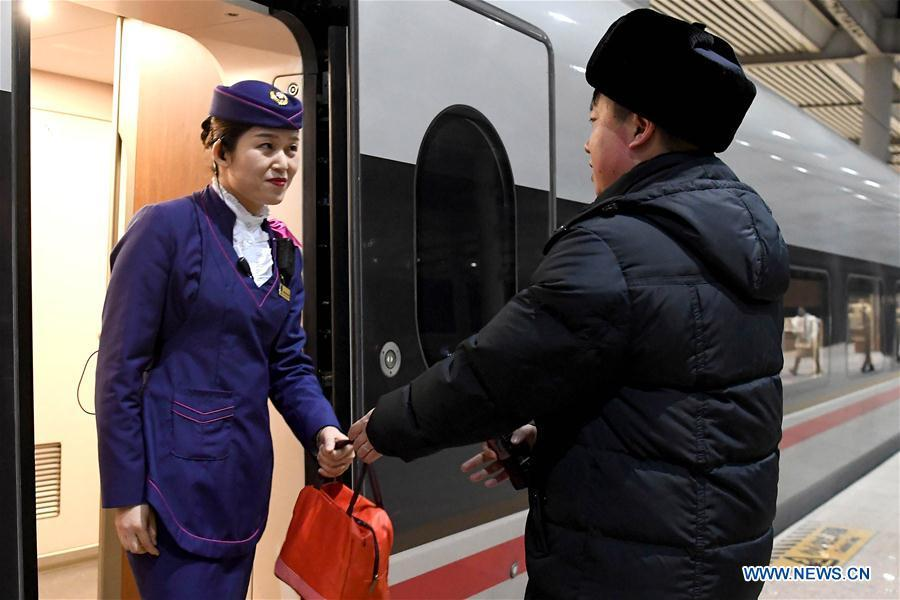 After finishing his work, Li Xiang (R) gives a lunch bag to his wife, Zou Xiaojuan during a temporary stop of the train No. G402 at Xinxiangdong Railway Station in Xinxiang City, central China\'s Henan Province, Jan. 22, 2019. Li Xiang is a staff worker of Xinxiangdong Railway Station and his wife Zou Xiaojuan is a train conductor on the train No. G402. The two-minute stop of the train No. G402 at Xinxiangdong Railway Station is their precious quality time in the bustle during the Spring Festival travel rush. (Xinhua/Li An)