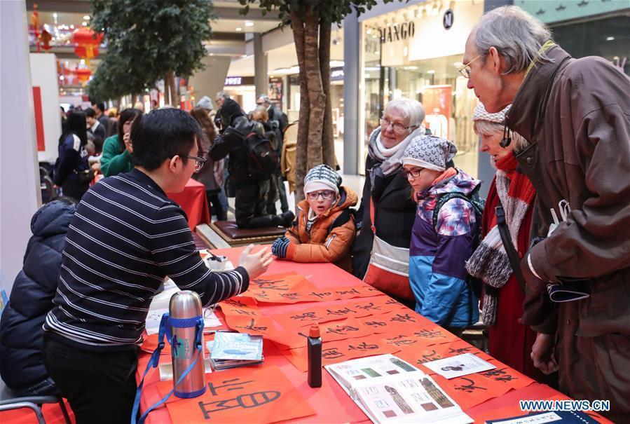 A staff member introduces Chinese Spring Festival couplets to visitors in a shopping mall at Potsdamer Platz in Berlin, capital of Germany, on Jan. 24, 2019. \