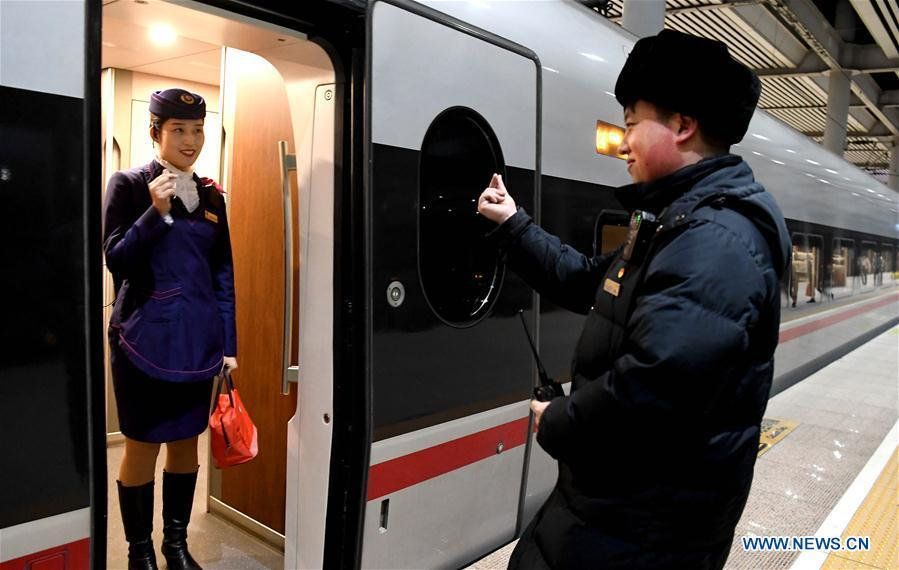 Li Xiang and his wife, Zou Xiaojuan, pose a gesture symbolizing \'love\' to each other before the departure of the train No. G402 at Xinxiangdong Railway Station in Xinxiang City, central China\'s Henan Province, Jan. 22, 2019. Li Xiang is a staff worker of Xinxiangdong Railway Station and his wife Zou Xiaojuan is a train conductor on the train No. G402. The two-minute stop of the train No. G402 at Xinxiangdong Railway Station is their precious quality time in the bustle during the Spring Festival travel rush. (Xinhua/Li An)