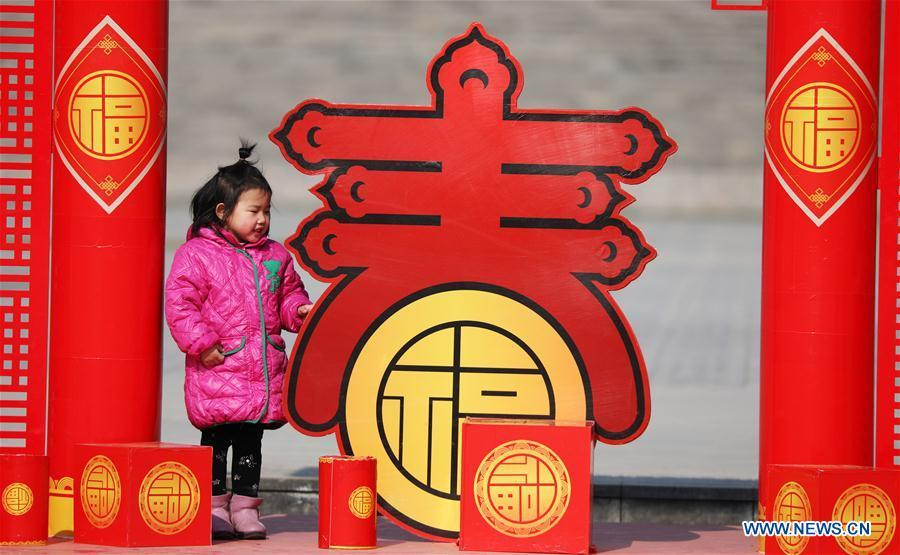 A girl is attracted by a lunar New Year decoration in Tancheng County of Linyi City, east China\'s Shandong Province, Jan. 24, 2019. Festive decorations are set up across China to greet the lunar New Year, or Spring Festival, which starts from Feb. 5 this year. (Xinhua/Zhang Chunlei)