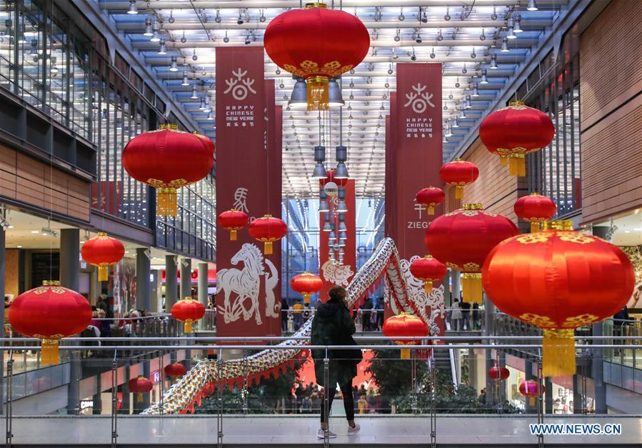 A woman walks past traditional Chinese decorations in a shopping mall at Potsdamer Platz in Berlin, capital of Germany, on Jan. 24, 2019. \