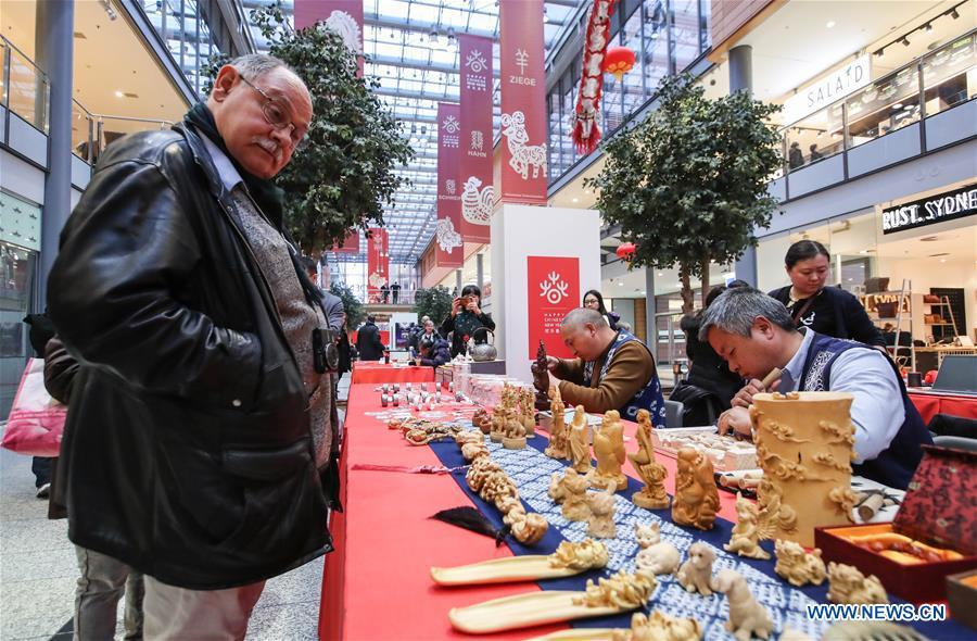 A visitor looks at traditional Chinese wood carvings in a shopping mall at Potsdamer Platz in Berlin, capital of Germany, on Jan. 24, 2019. \