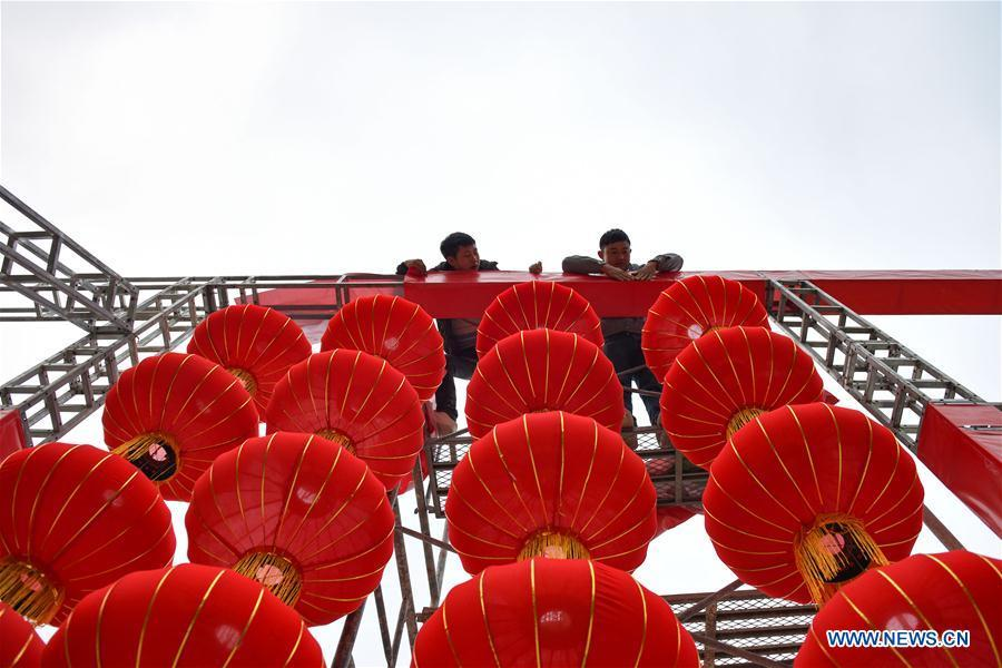 Workers erect red lanterns on the Xinglong Square of Longli County in Bouyei-Miao Autonomous Prefecture of Qiannan, southwest China\'s Guizhou Province, Jan. 24, 2019. Festive decorations are set up across China to greet the lunar New Year, or Spring Festival, which starts from Feb. 5 this year. (Xinhua/Long Yi)