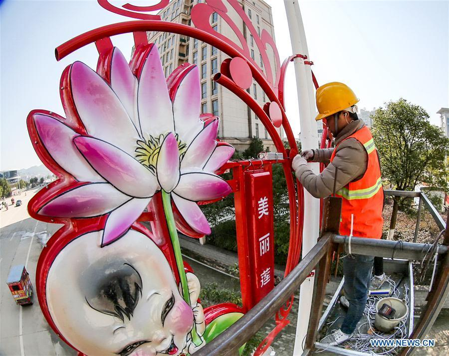 A worker sets up a festive lantern on a street in Guangchang County of Fuzhou City, east China\'s Jiangxi Province, Jan. 24, 2019. Festive decorations are set up across China to greet the lunar New Year, or Spring Festival, which starts from Feb. 5 this year. (Xinhua/Zeng Henggui)