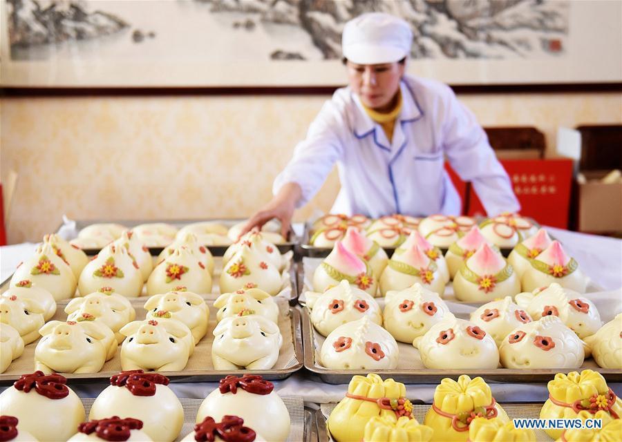 A villager takes buns off a shelf, which are made to celebrate the lunar New Year in Shengjiazhuang Village, Jiaozhou City of east China\'s Shandong Province, Jan. 24, 2019. (Xinhua/Wang Zhaomai)