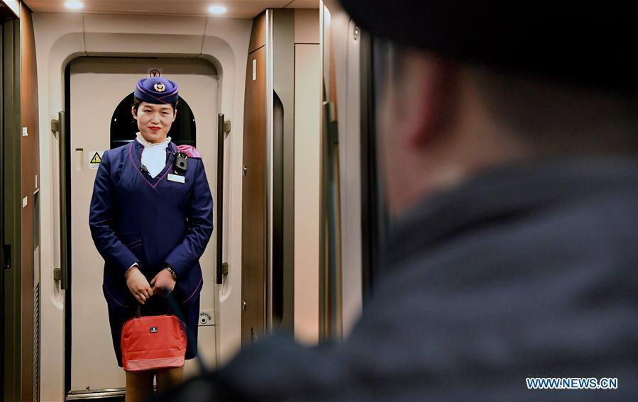After receiving the lunch box, Li Xiang\'s wife, Zou Xiaojuan, smiles at Li during a temporary stop of the train No. G402 at Xinxiangdong Railway Station in Xinxiang City, central China\'s Henan Province, Jan. 22, 2019. Li Xiang is a staff worker of Xinxiangdong Railway Station and his wife Zou Xiaojuan is a train conductor on the train No. G402. The two-minute stop of the train No. G402 at Xinxiangdong Railway Station is their precious quality time in the bustle during the Spring Festival travel rush. (Xinhua/Li An)
