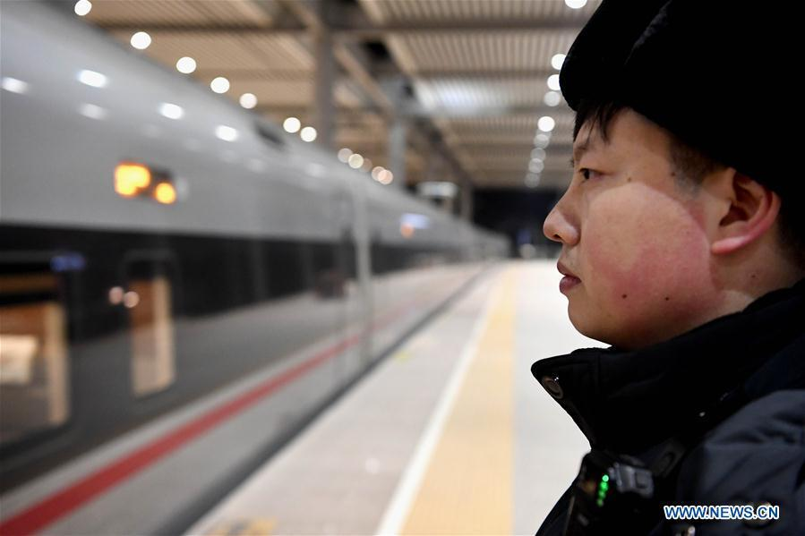 Li Xiang watches the departure of the train No. G402 after its temporary stop at Xinxiangdong Railway Station in Xinxiang City, central China\'s Henan Province, Jan. 22, 2019. Li Xiang is a staff worker of Xinxiangdong Railway Station and his wife Zou Xiaojuan is a train conductor on the train No. G402. The two-minute stop of the train No. G402 at Xinxiangdong Railway Station is their precious quality time in the bustle during the Spring Festival travel rush. (Xinhua/Li An)