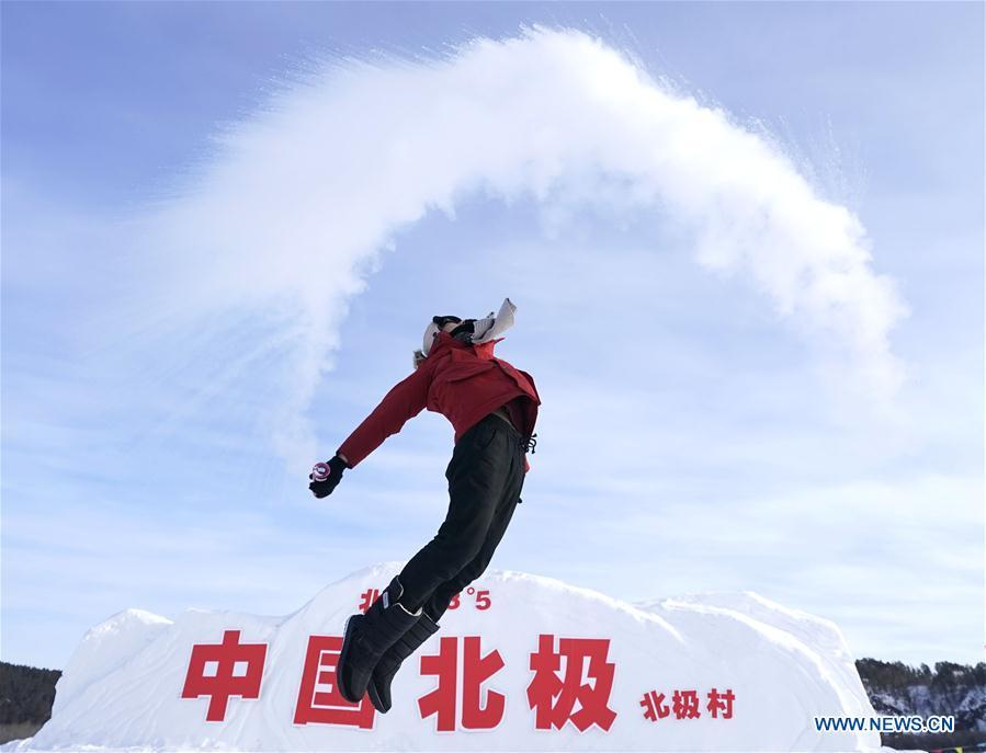 A visitor plays a game with water spray in Beiji Village, Mohe City of northeast China\'s Heilongjiang Province, Jan. 24, 2019. With the lowest temperature approaching minus 30 degrees celsius, visitors in Mohe Village experienced the game of \