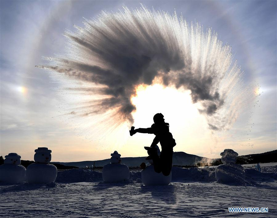 A visitor creates an ice halo with water spray in Beiji Village, Mohe City of northeast China\'s Heilongjiang Province, Jan. 24, 2019. With the lowest temperature approaching minus 30 degrees celsius, visitors in Mohe Village experienced the game of \