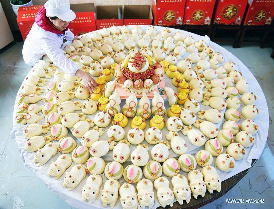 A villager arranges steamed buns made to celebrate the lunar New Year in Shengjiazhuang Village, Jiaozhou City of east China\'s Shandong Province, Jan. 24, 2019. (Xinhua/Wang Zhaomai)