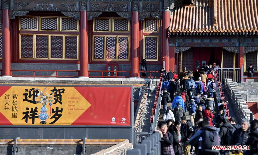 Tourists walk past a poster celebrating the Spring Festival in the Palace Museum, also known as the Forbidden City, in Beijing, capital of China, Jan. 25, 2019. The Palace Museum is decorated to celebrate the upcoming Spring Festival, or the Chinese Lunar New Year, which falls on Feb. 5 this year. (Xinhua/Li Xin)