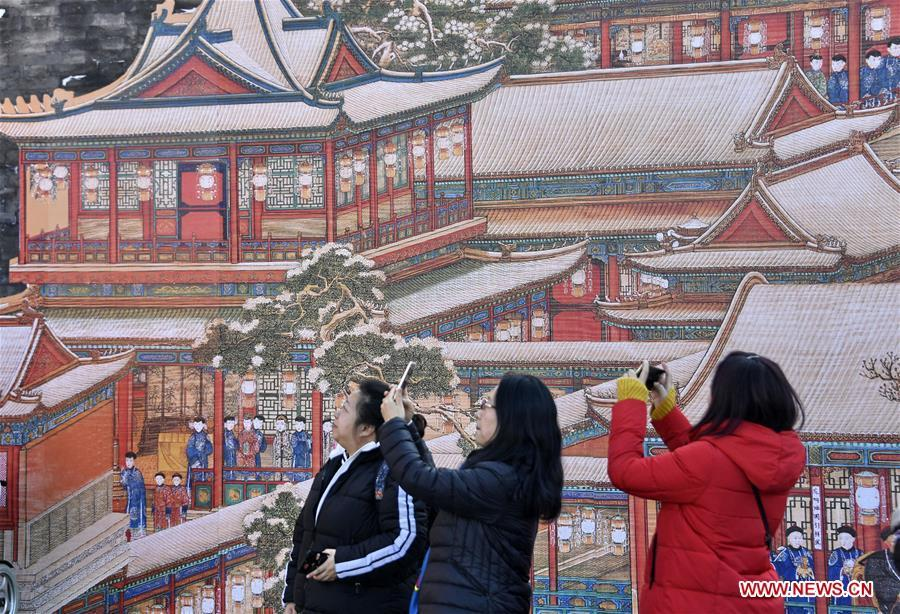 Tourists take photos of paintings in the Palace Museum, also known as the Forbidden City, in Beijing, capital of China, Jan. 25, 2019. The Palace Museum is decorated to celebrate the upcoming Spring Festival, or the Chinese Lunar New Year, which falls on Feb. 5 this year. (Xinhua/Li Xin)