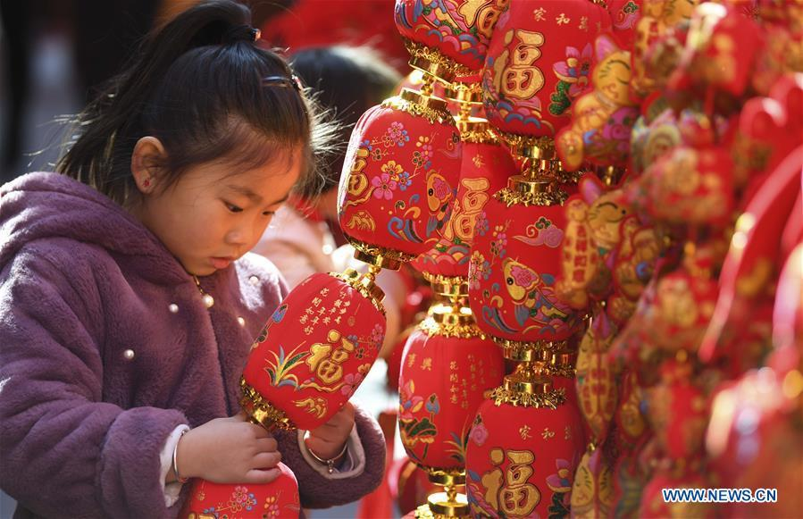 A child looks at Spring Festival decoration at a market in Hefei, capital of east China\'s Anhui Province, Jan. 26, 2019. Red decorations are arranged across China to greet the upcoming lunar New Year which will fall on Feb. 5 this year. (Xinhua/Liu Qinli)