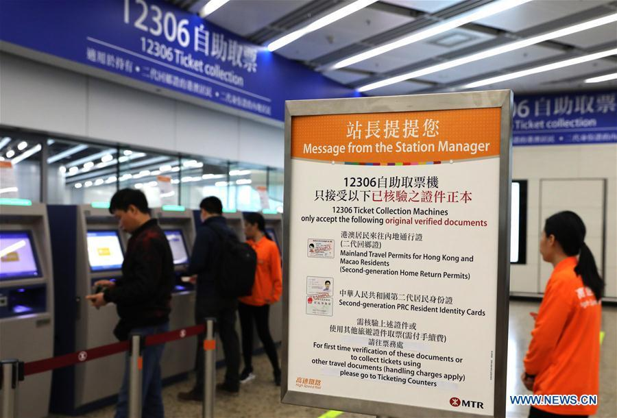 Passengers take their tickets from automotive ticket machines at the West Kowloon railway station in Hong Kong, south China, Jan. 25, 2019. To better serve the passengers using the automotive ticket machines, blue signs are installed and staff members in orange are dispatched to offer help at the West Kowloon railway station in Hong Kong. (Xinhua/Wu Xiaochu)