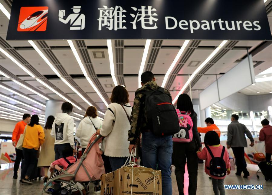 Passengers wait at the departure area in the West Kowloon railway station in Hong Kong, south China, Jan. 25, 2019. To better serve the passengers using the automotive ticket machines, blue signs are installed and staff members in orange are dispatched to offer help at the West Kowloon railway station in Hong Kong. (Xinhua/Wu Xiaochu)